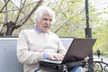 Senior man using laptop computer outdoors Royalty Free Stock Photo