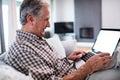 Senior man using laptop in living room Royalty Free Stock Photo