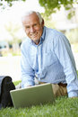 Senior man using laptop outdoors Royalty Free Stock Photo