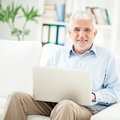 Senior man using laptop smiling men sitting in his living room and his Royalty Free Stock Photography