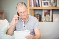 Senior man using mobile phone while looking documents at home Royalty Free Stock Photos