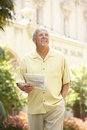Senior Man Walking Through City Street With Map Royalty Free Stock Image