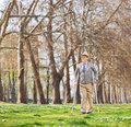 Senior man walking with crutches outdoors shot tilt and shift lens Royalty Free Stock Image