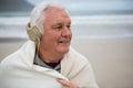Senior man wearing shawl and listening music on headphones Royalty Free Stock Photo