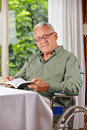 Senior man in wheelchair with book Stock Photos
