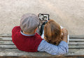 A senior man and woman hand using a touchscreen cell phone Royalty Free Stock Photo
