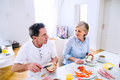 Senior man and woman having breakfast. Sunny morning. Royalty Free Stock Photo
