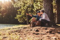 Senior man and woman on a hike in nature mature couple sitting by tree forest with men showing something to men women summer Royalty Free Stock Photo