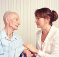 Senior man woman with their caregiver at home concept of health care for elderly old people disabled Stock Photography