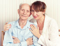 Senior man woman with their caregiver at home concept of health care for elderly old people disabled Royalty Free Stock Photos