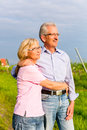 Senior man and woman walking hand in hand couple having a walk summer or outdoors the vineyard Royalty Free Stock Photography