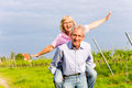 Senior man and woman walking hand in hand couple having a walk summer or outdoors the vineyard Stock Photo