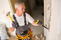 Senior man working with hammer and tool while demolish wall Royalty Free Stock Photo