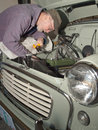 Senior man working on vintage car making adjustments to the engine of a he is restoring Stock Image