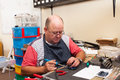 Senior man workshop working with soldering iron in Stock Photography