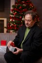 Senior man wrapping christmas gift sitting on couch at home concentrating Stock Images