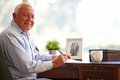 Senior man writing memoirs in book sitting at desk looking camera smiling Royalty Free Stock Images