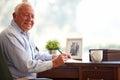 Senior Man Writing Memoirs In Book Sitting At Desk Royalty Free Stock Photo