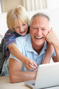 Senior man with young boy using laptop computer Royalty Free Stock Photo
