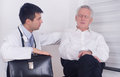 Senior man with young doctor men talking about pain and symptoms to male Stock Photo