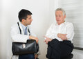 Senior man with young doctor men talking about symptoms to male Royalty Free Stock Photography