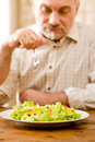 Senior mature man eat vegetable salad Royalty Free Stock Photos
