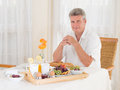Senior mature man sitting down to a healthy breakfast looking at camera men with tray of fresh fruit eggs and coffee as he looks Royalty Free Stock Photos