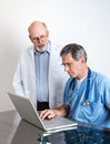 Senior medical doctors discussing patient s mri film scans at laptop computer Stock Photos