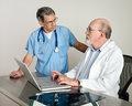 Senior medical doctors discussing patient s mri film scans at laptop computer short depth of field doctor in background in soft Royalty Free Stock Images