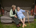 Senior mom and daughter sharing a laugh an edlerly with her visiting while sitting on swing outdoors Stock Images