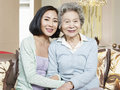 Senior mother and adult daughter asian sitting on couch smiling Stock Photo