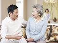 Senior mother and adult son asian chatting on couch Stock Image