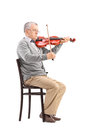 Senior musician playing a violin an acoustic seated on wooden chair isolated on white background Royalty Free Stock Images
