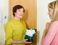 Senior neighbor presenting gift to young girl smiling in door of home Royalty Free Stock Photography