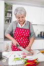 Senior or older woman with grey hair cooking in kitchen. Royalty Free Stock Image