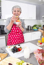 Senior or older woman with grey hair cooking in kitchen - Desser Stock Image