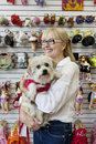 Senior pet shop owner standing with dog Stock Photography