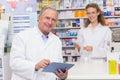 Senior pharmacist using tablet pc at the hospital pharmacy Stock Photo