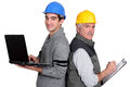 Senior plumber and junior standing back to back with laptop clipboard Royalty Free Stock Images