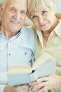 Senior readers portrait of a candid couple looking at camera while reading book together Royalty Free Stock Photography