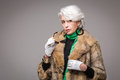 Senior rich woman portrait of holding sunglasses in front of her vogue lady in fur coat posing in studio on grey background Stock Photos