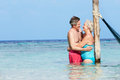 Senior romantic couple standing in beautiful tropical sea hugging Stock Photos