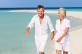 Senior romantic couple walking on beautiful tropical beach holding hands Royalty Free Stock Image