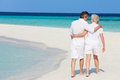 Senior romantic couple walking on beautiful tropical beach in the sun Stock Images