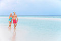 Senior romantic couple walking in beautiful tropical sea holding hands Stock Photos