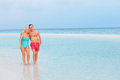 Senior romantic couple walking in beautiful tropical sea smiling Stock Image