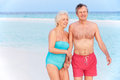 Senior romantic couple walking in beautiful tropical sea smiling Stock Images