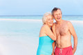 Senior romantic couple walking in beautiful tropical sea smiling Stock Photography