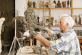 Senior sculptor making sculpture sideview Royalty Free Stock Photos