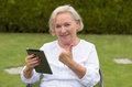 Senior serene woman using a black tablet pc wearing white shirt and sitting on chair on the green lawn of the garden while Royalty Free Stock Photography